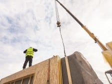 Roofer builder worker with crane installing structural Insulated Panels SIP.